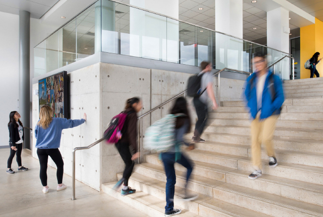 Students walking up and down stairs in a building