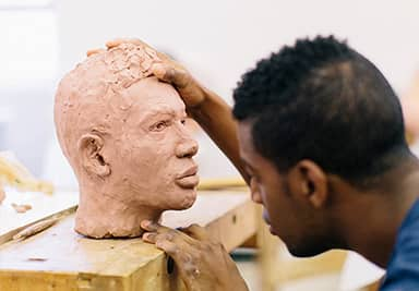 A student sculpting a head made of clay