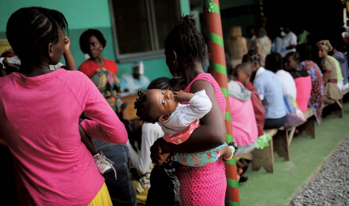 Mother bringing her sick child for treatment in Liberia during 2015 Ebola outbreak