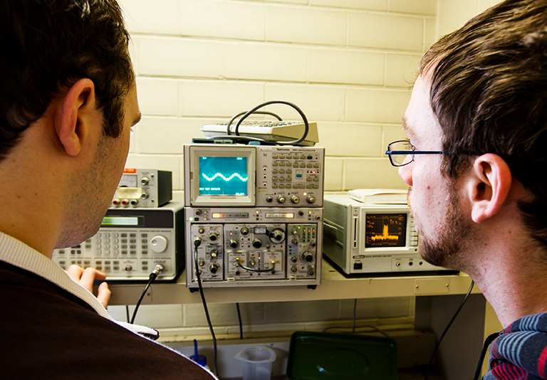 Two people looking at a waveform