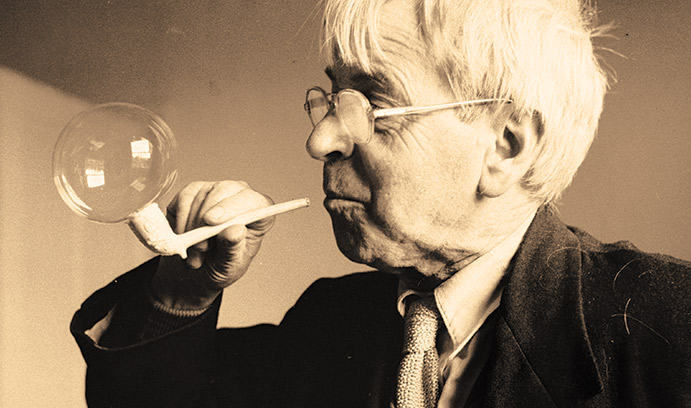 Man blowing bubble into pipe