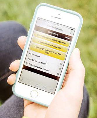 Student's hand holding an iphone displaying the Emergency section of the Lehigh app