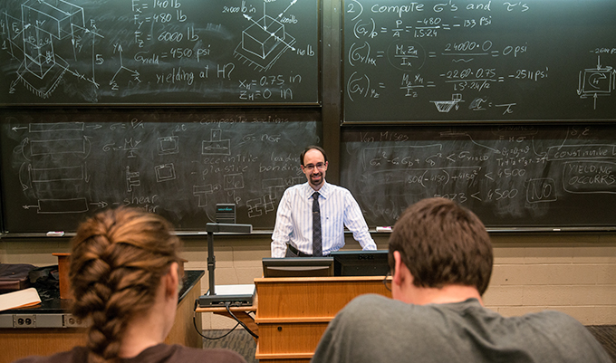professor standing in front of chalk board