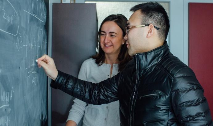 Sera Cremonini, assistant professor of physics at Lehigh, solves string theory problems with postdoctoral researcher Li Li.