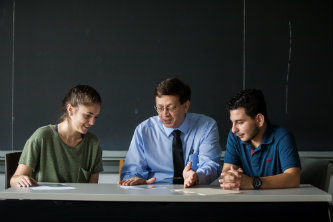 Associate professor of physics Jerome Licini (center) shows Florencia Dayan '21 (left) and George Awad '22 (right) how to use his tilted-axes tool.