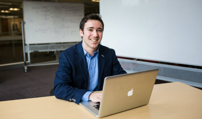 Lehigh University student Ben Mesnik sits at table with laptop