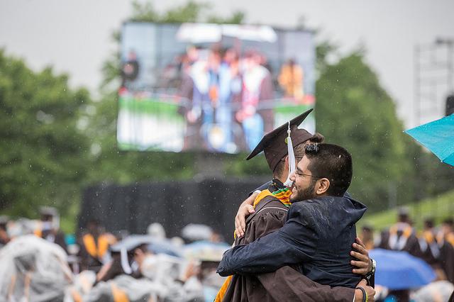 Graduate hugging family member