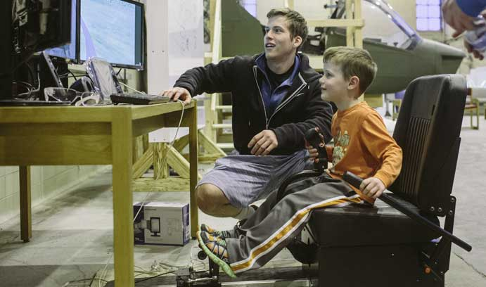 Marty Melochick '15 shows 5-year-old Sully Hochbein the controls.