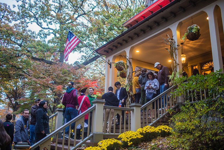 Students and their families at the President's house for a Halloween party
