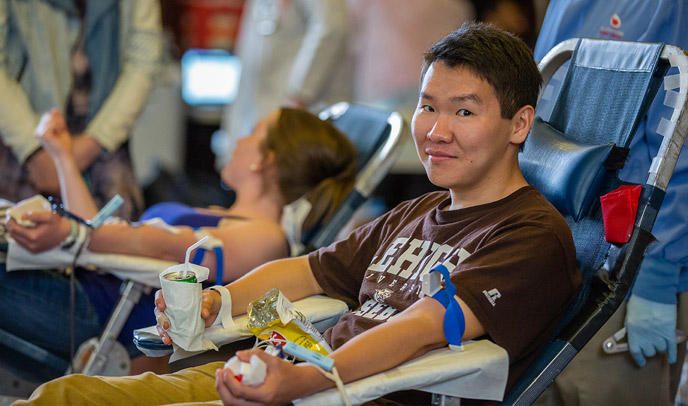 student giving blood at blood drive