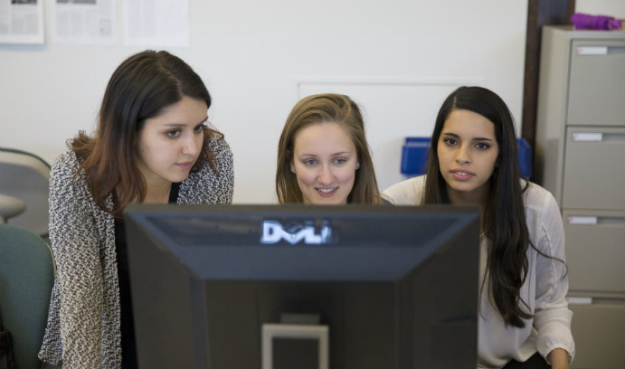Three editors for The Brown and White student newspaper gather around a laptop