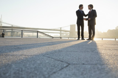Two men shake hands in front of a bridge