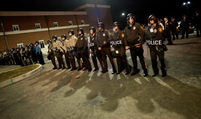 Law enforcement officers stand guard during a protest at the Ferguson Police Department in Ferguson, Mo.