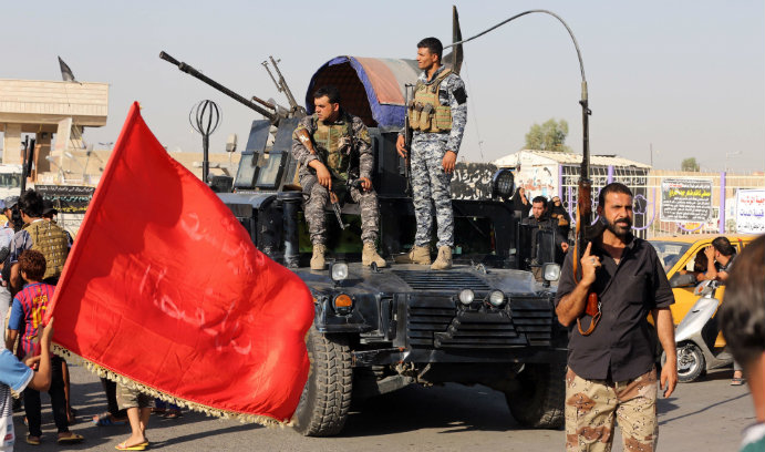 Iraqi federal policemen watch as Shiite tribal fighters deploy with their weapons in the northwest Baghdad's Shula neighborhood, Iraq, Monday, June 16, 2014. Sunni militants captured a key northern Iraqi town along the highway to Syria early on Monday, co