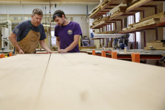Brian Slocum, left, and wood shop Manager Michael Moore work on a conference tabled made from Lehigh's felled trees. Slocum didn't want a gust of wind to end the trees' significance to Lehigh.