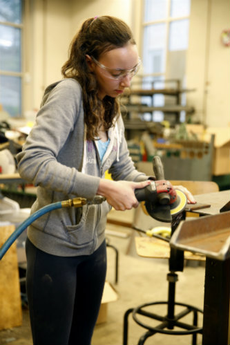 Mechanical engineering student Deanna Shepherd helped chip off bark from the rough wood, sand the table tops and cut the pieces for the steel base.