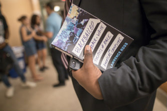 A man holding Lawrence Ross' book, Blackballed.
