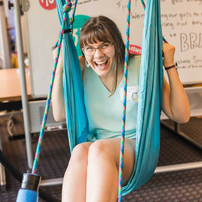 Student sitting in a swing