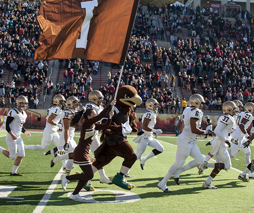 The Lehigh football team running on a football field with Clutch, Lehigh's mascot