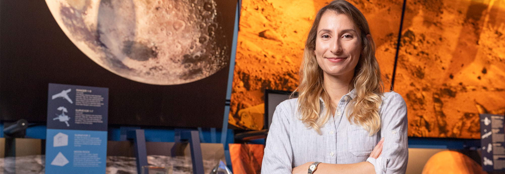Pam Fusek '13 standing beside a photograph of the moon.