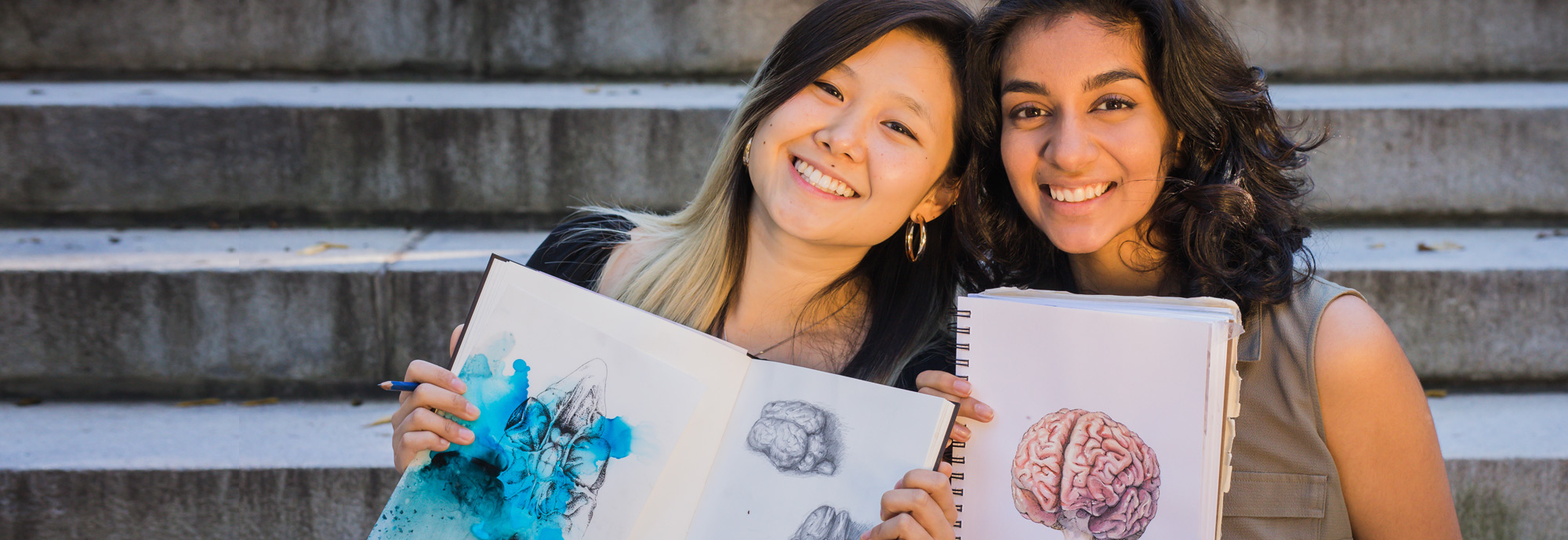 Two students holding brain portraits