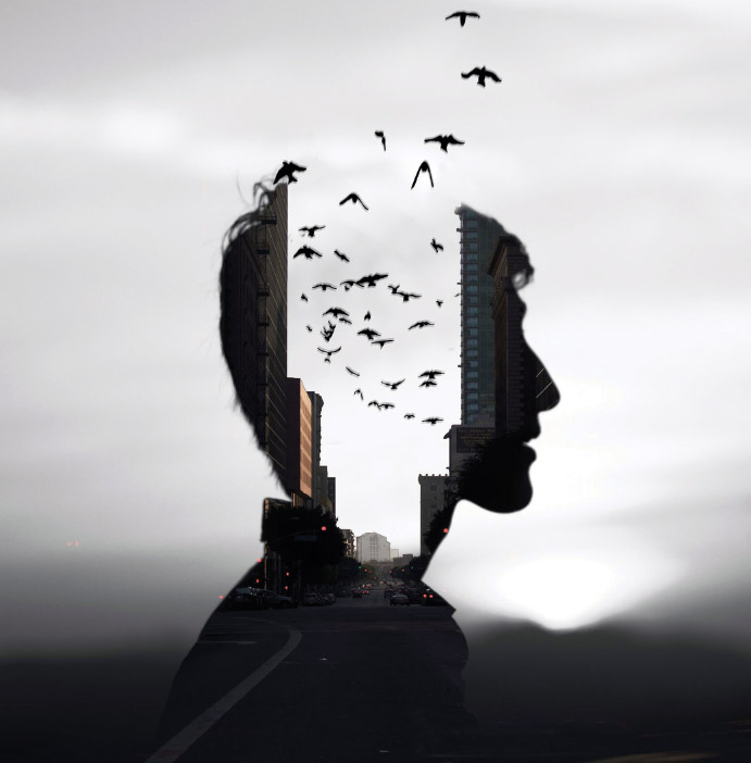 Artistic photograph of a young man's head that appears to be open with a city inside and birds flying out.