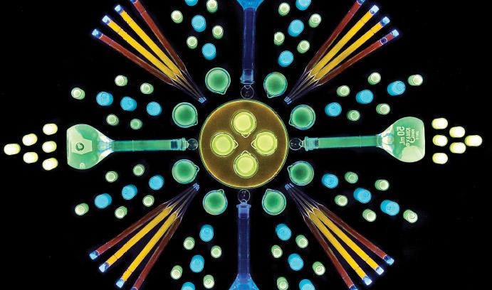 Colorful beakers and test tubes of quantum dots under black light in mandala arrangement.