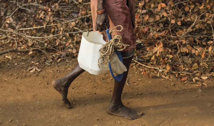 A barefoot woman carries a bucket of water in Africa