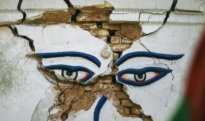 A painting of a face on a brick wall shows cracks after an earthquake.