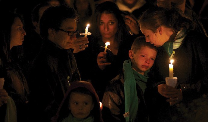 Children and adults mourning at a candlelight vigil.