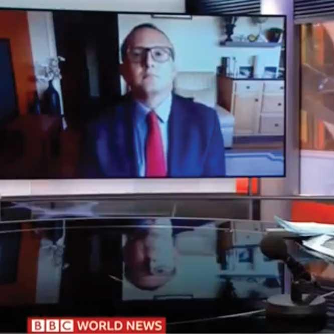 Eduardo Gomez talking on BBC shown on a TV screen