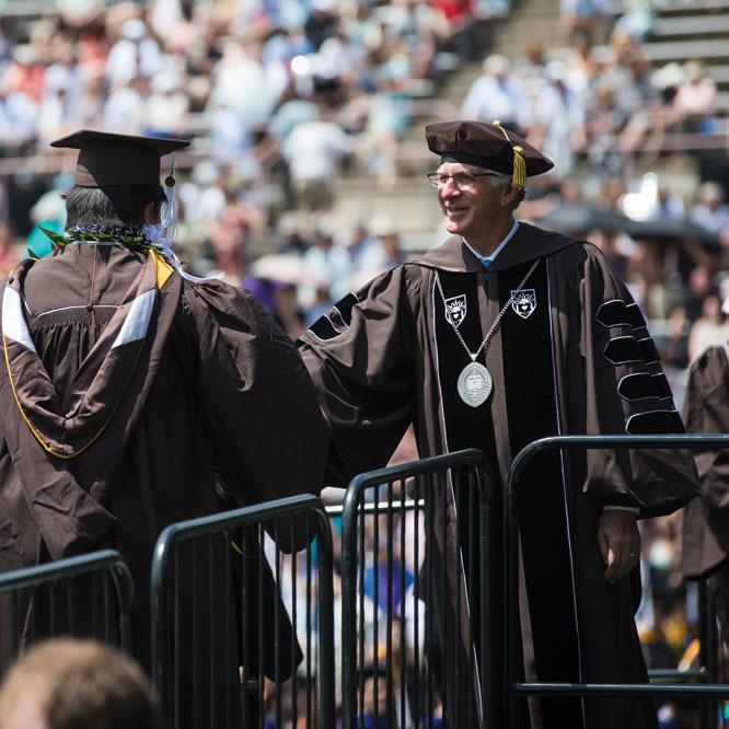 President John D. Simon congratulates students as they receive their degrees.