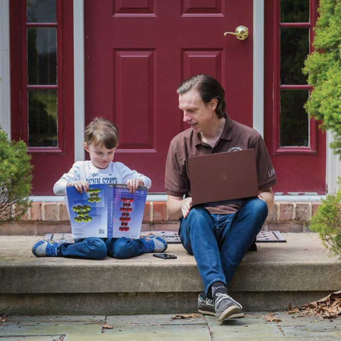 Professor Nick Strandwitz sitting with his son on his porch