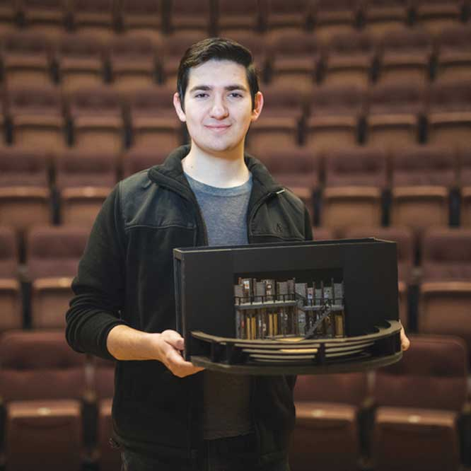 Travis Martinez holding a set design model