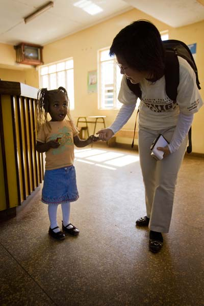 Xuanhong Cheng talks with a young girl during her visit to the Karuri Health Centre in Kenya