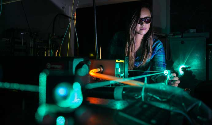 In her research, Courtney Au-Yeung shines diode lasers onto chalcogenide glass until the heat from the laser causes the glass to nucleate into single crystals. (Photo by Christa Neu)