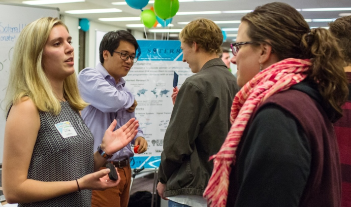 Lena McDonnell '18 (left) and Michael Wu '20 (second from left) explain the Soterra advantage to visitors at CREATIVATE. Soterra uses mesh networking to provide women with access to emergency response services. (Photo by Christa Neu)