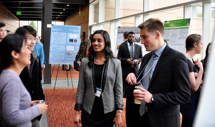 Kathryn Kundrod '15 (center) and Jay Fraser '15 (right) discuss their HIV medication-monitoring technology with visitors at the Freed Undergraduate Research Symposium.