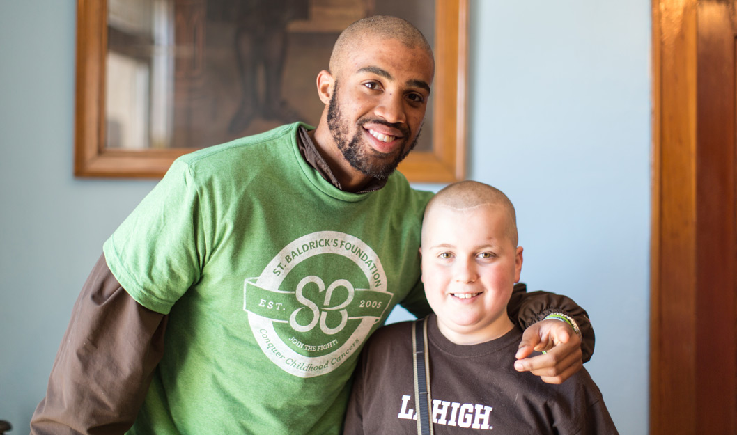 Lehigh football player with a child at the Shave for the Brave event, an event to raise money for child cancer research.