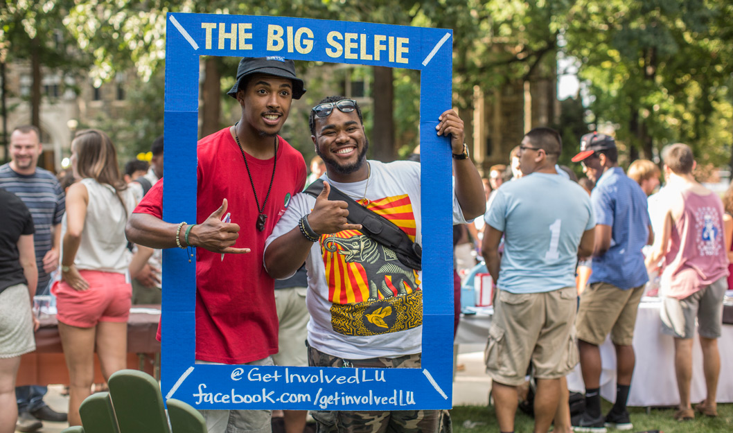 """Two students having their picture taken holding a frame that says """"The Big Selfie"""""""