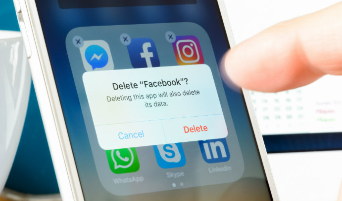 A smartphone screen with a prompt to delete Facebook