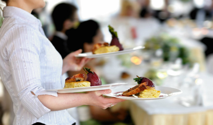 Image of a restaurant server holding a tray of food.