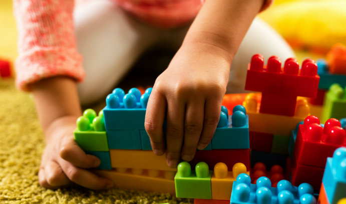 Child playing with brightly colored LEGO blocks.