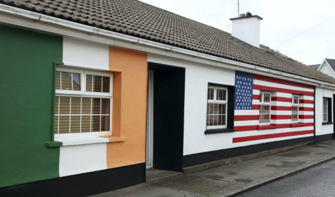 Building with the flag of Ireland on the left and the American flag on the right