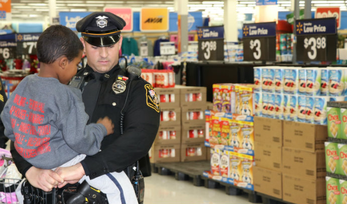 LUPD Officer Scott Ednie escorts a local child during the Shop with a Cop event at a nearby Walmart.