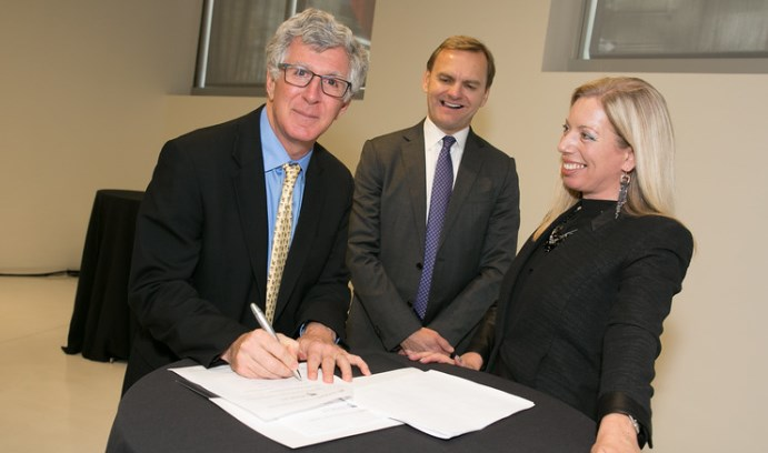 Lehigh President John Simon (left) signs a partnership document as Bruce Aust (center), vice president of Nasdaq and president of the Nasdaq Entrepreneurial Center, and Nicola Corzine, executive director of the Center, look on.