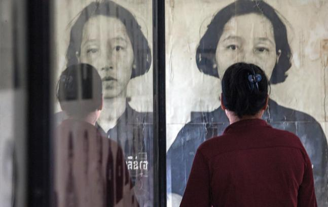 A Cambodian survivor stands in front of the photograph of a prisoner at a former Khmer Rouge prison. (Photo courtesy of Omar Havana/Getty Images)