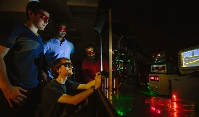 Philip Vendola '16 (left) and Wesley Pierre '16 (center, top) watch as Blades (below) and Rotkin (right) use a Raman microscopy system to find and quantify the properties of a single layer of graphene that has been carefully transferred onto a soft-matter