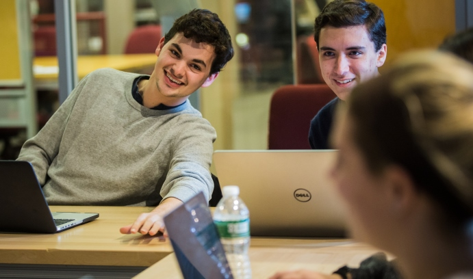 Hardware team lead Matt Ciolino '18 (left), a mechanical engineering major, and team member Ian Ferguson '18, an electrical engineering major, share a light moment with Randolph (foreground).
