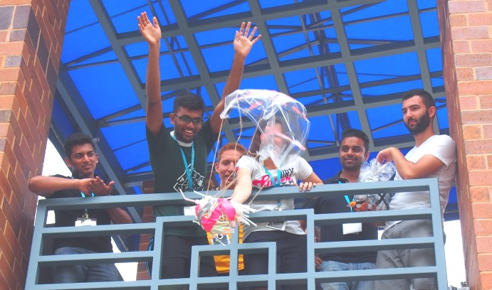 Munisrau Krishnapparao of Malaysia raises his arms as Melanie Lianzon of France releases the cargo during the egg-drop contest. In the background, are Afif Shaikh of India, Ricardo Franklin of Colombia, Bittu Thakur of India and Vadim Abanin of Tajikistan
